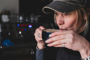 Close up of blond woman wearing baseball cap drinking cappuccino.の写真素材 [FYI02266477]