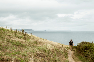 Rear view of a man in walking boots with a rucksack, walking along a coastal path, and a sea view.の写真素材 [FYI02266480]