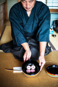 Japanese man wearing traditional kimono knelling on floor, holding a bowl with Wagashi, sweets tradiの写真素材 [FYI02266488]