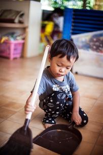 Girl using broom and dustpan in a Japanese preschool.の写真素材 [FYI02266489]
