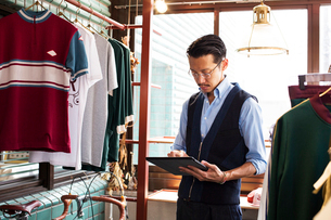 Japanese salesman with moustache wearing glasses standing in clothing store, looking at digital tablの写真素材 [FYI02266490]