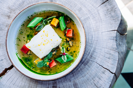Pouring broth on halibut with lemon, peas, melon, beets and herbsの写真素材 [FYI02266494]