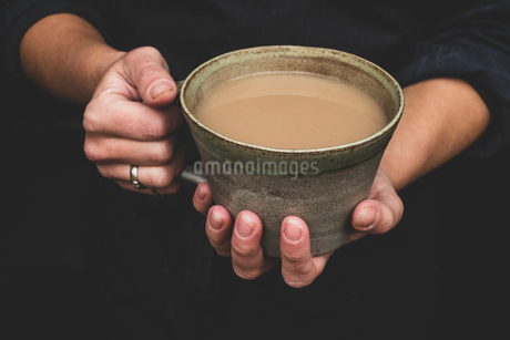 High angle close up of human hands holding green earthenware mug of tea.の写真素材 [FYI02266495]