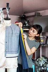Japanese female fashion designer working on a garment on a dressmaker's model in a studio.の写真素材 [FYI02266503]
