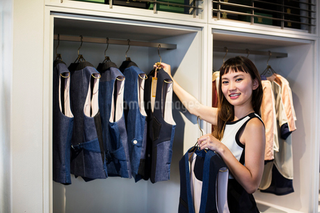 Japanese saleswoman standing in clothing store, hanging blue waistcoats on rail, smiling at camera.の写真素材 [FYI02266515]