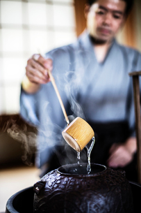 Close up of traditional Japanese Tea Ceremony, man using a Hishaku, a bamboo ladle, to pour hot wateの写真素材 [FYI02266519]