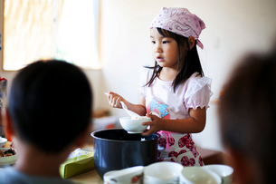 Girl wearing headscarf standing at a table in a Japanese preschool, serving lunch to children.の写真素材 [FYI02266522]