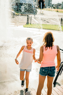 Smiling girls playing in public fountain in summerの写真素材 [FYI02266523]