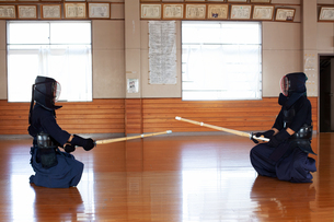 Two Japanese Kendo fighters sitting opposite each other on wooden floor, wearing Kendo masks and holの写真素材 [FYI02266528]