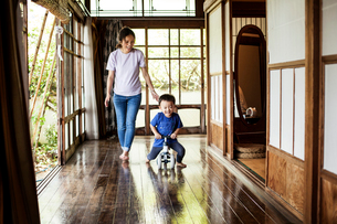 Smiling Japanese woman and little boy on a tricycle on porch of traditional Japanese house.の写真素材 [FYI02266529]