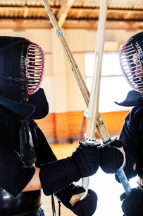 Two Japanese Kendo fighters wearing Kendo masks practicing with wood sword in gym.の写真素材 [FYI02266530]