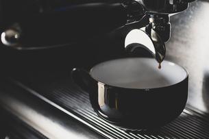 Close up of black mug on espresso machine.の写真素材 [FYI02266531]