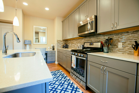 Modern home kitchen with green grey fitted units, a kitchen island and blue floor rug.の写真素材 [FYI02266532]