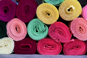 Close up of a selection of rolls of fabric in various colours.の写真素材 [FYI02266542]