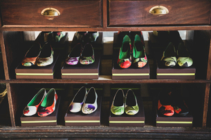 High angle close up of heeled shoes with colourful floral patterns on brown boxes lined up on woodenの写真素材 [FYI02266544]