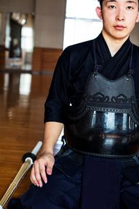 Male Japanese Kendo fighter kneeling on floor, looking at camera.の写真素材 [FYI02266560]