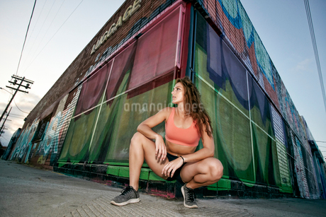 Female athlete kneeling on sidewalk in front of boarded up building covered in graffiti.の写真素材 [FYI02266569]