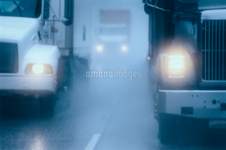 Partial view of large commercial truck driving in hazardous conditions of snow and rain on a freewayの写真素材 [FYI02266571]