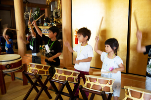 Group of pre-school children playing the drums in a Japanese temple, a traditional religious practisの写真素材 [FYI02266578]