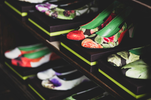 High angle close up of heeled shoes with colourful floral patterns on brown boxes lined up on woodenの写真素材 [FYI02266586]