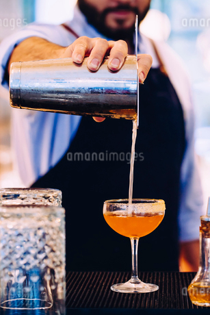 Bartender pouring whiskey cocktail into glass with sugared rimの写真素材 [FYI02266591]