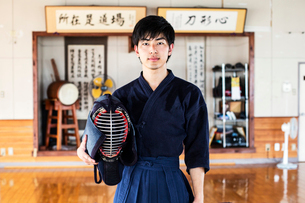 Male Japanese Kendo fighter standing in a gym, holding Kendo mask, looking at camera.の写真素材 [FYI02266596]