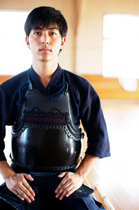 Male Japanese Kendo fighter kneeling on floor, looking at camera.の写真素材 [FYI02266600]