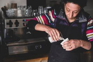 Woman behind espresso machine pouring hot milk into paper cup.の写真素材 [FYI02266610]