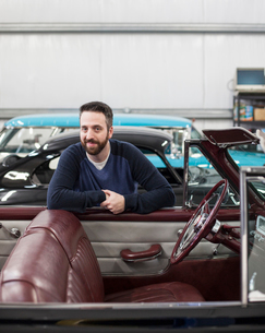 A portrait of a Caucasian male leaving on the side of his classic car convertible in a repair shop.の写真素材 [FYI02266616]