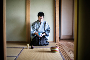 Japanese man wearing traditional kimono kneeling on tatami mat, holding tea bowl, during tea ceremonの写真素材 [FYI02266622]