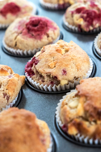 High angle close up of raspberry and white chocolate muffins in a baking tray.の写真素材 [FYI02266623]