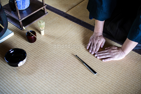 High angle close up of Japanese man kneeling on tatami mat in front of Sensu fan, bowl and whisk useの写真素材 [FYI02266626]