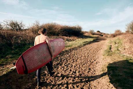 Man holding surf board walking along sandy path towards beachの写真素材 [FYI02266628]