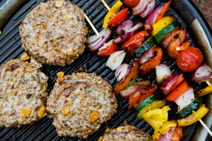 Food on a barbeque, vegetable kebabs and home made burgers, cooking outdoors.の写真素材 [FYI02266636]