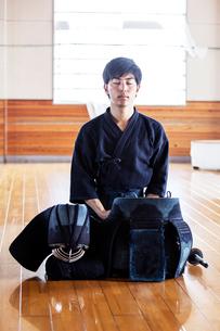 Male Japanese Kendo fighter kneeling on wooden floor, meditating.の写真素材 [FYI02266639]