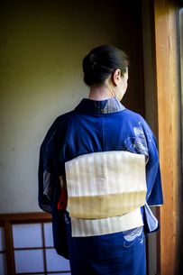 Rear view of Japanese woman wearing traditional bright blue kimono with cream coloured obi.の写真素材 [FYI02266644]
