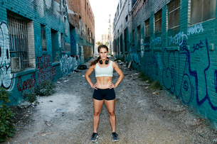Female athlete standing on street lined with buildings covered in graffiti.の写真素材 [FYI02266651]