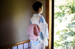 Rear view of Japanese woman standing at window, wearing traditional white kimono with blue floral paの写真素材 [FYI02266667]