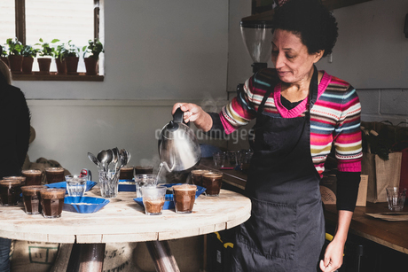 Coffee tasting, woman pouring coffee into glasses on a wooden table, trays with coffee beans.の写真素材 [FYI02266670]