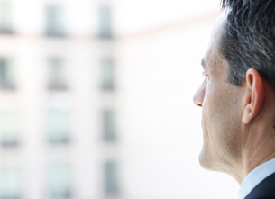 Closeup of a Caucasian businessman looking out the widow of a conference centre lobby.の写真素材 [FYI02266681]