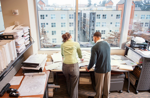 A view from behind of two people going over plans for a new space in their office.の写真素材 [FYI02266691]
