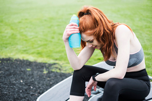 Young woman with long red hair wearing sports kit, exercising outdoors.の写真素材 [FYI02266698]