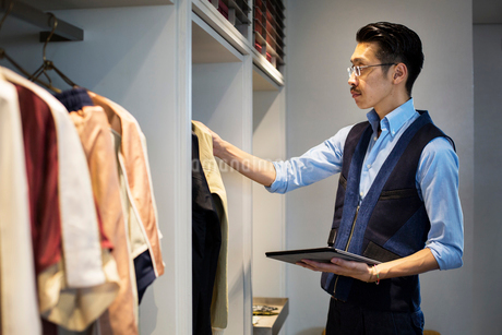Japanese salesman with moustache wearing glasses standing in clothing store, looking at clothes on aの写真素材 [FYI02266702]