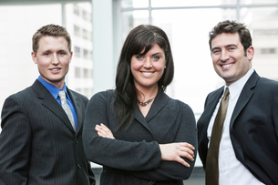 A group portrait of three business people, with a Caucasian woman as the lead.の写真素材 [FYI02266707]