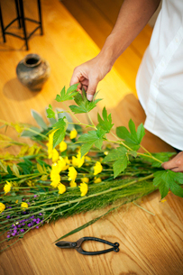 Person in a flower gallery, working on Ikebana arrangement with leaves, yellow and purple flower.の写真素材 [FYI02266710]
