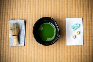 Tea ceremony utensils including bowl of green Matcha tea, a bamboo whisk and Wagashi sweets.の写真素材 [FYI02266715]