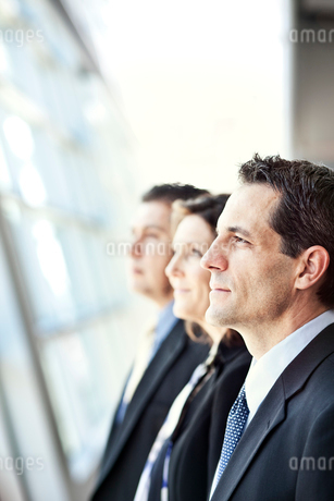 Group of three business people looking out the window of a conference centre lobby.の写真素材 [FYI02266726]