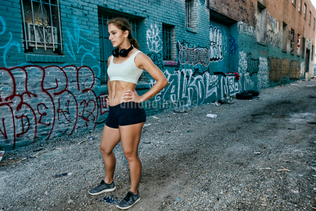 Female athlete standing on street in front of blue building covered in graffiti.の写真素材 [FYI02266735]