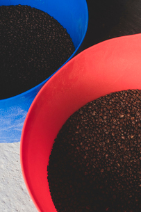 High angle close up freshly roasted coffee beans in blue and red buckets..の写真素材 [FYI02266738]