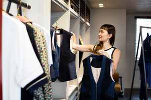 Japanese saleswoman standing in clothing store, hanging blue waistcoats on rail.の写真素材 [FYI02266748]